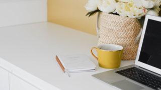 ノートPCとカップ、花が置かれたデスク