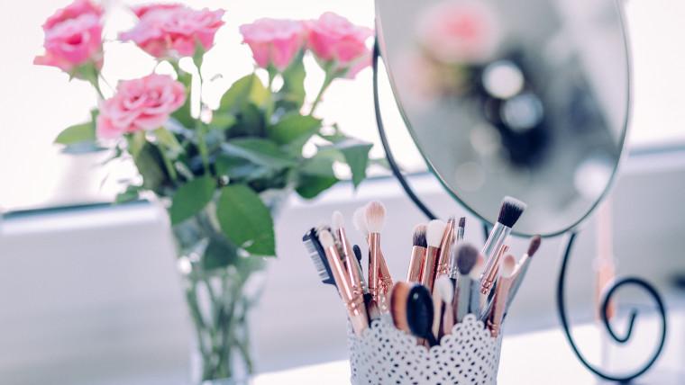鏡とメイクブラシと花が置かれたデスク