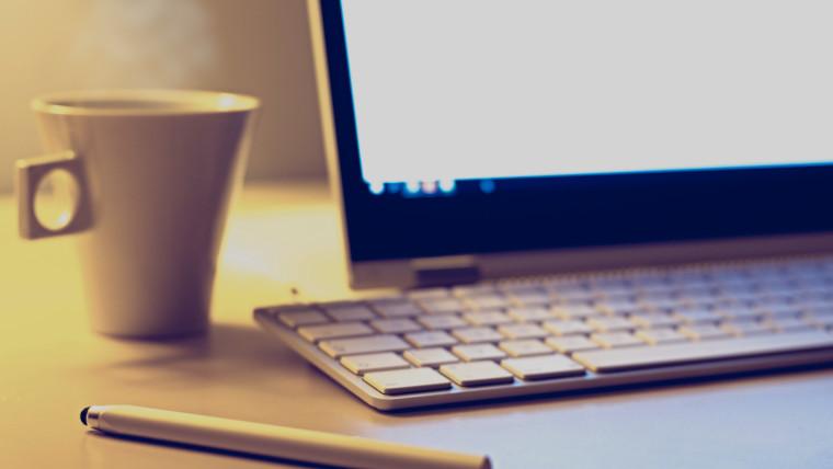 デスクの上のPCとコーヒーカップ